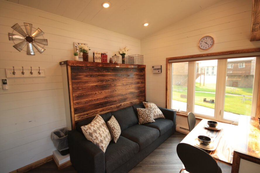 inteiror of tiny home with wooden accent wall behind a black sofa