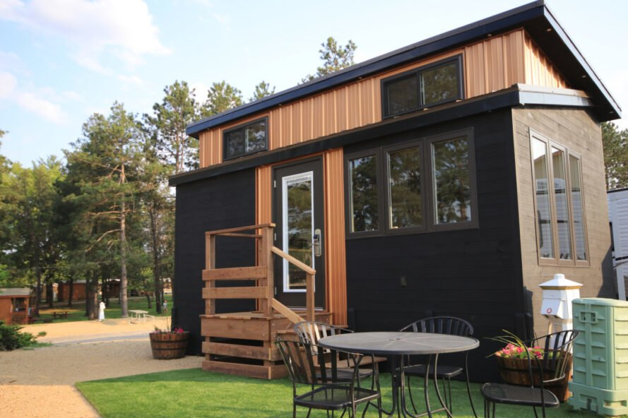 black and tan tiny home with windows and front stairwell