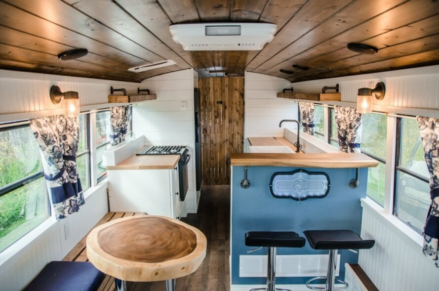 inside of a skoolie with white walls, wood ceilings