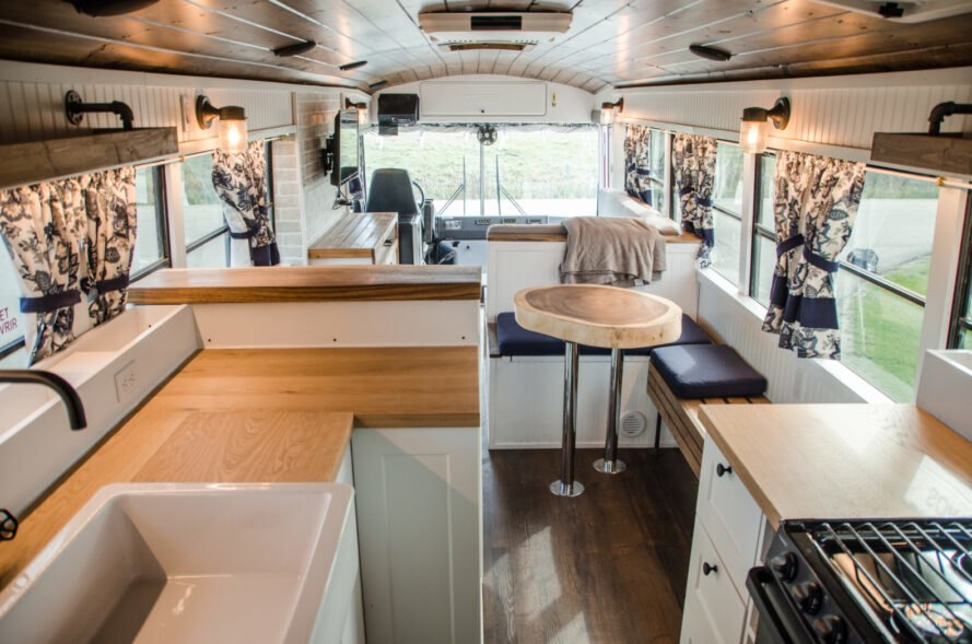 skoolie interior with dining table and kitchen