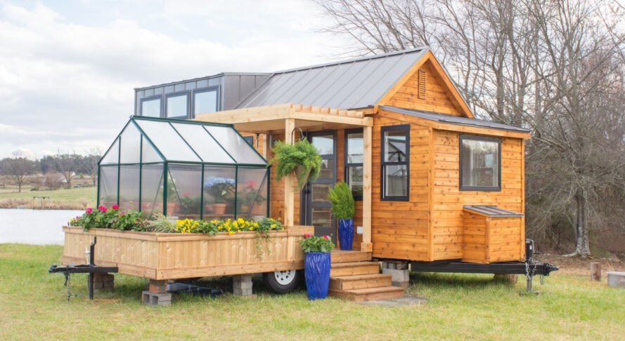 wooden tiny home with a greenhouse