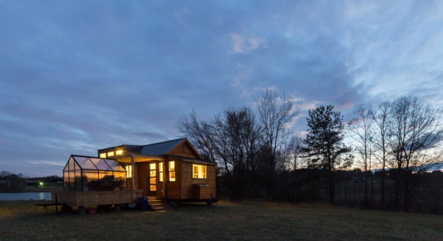 wooden tiny home with attached greenhouse at dusk
