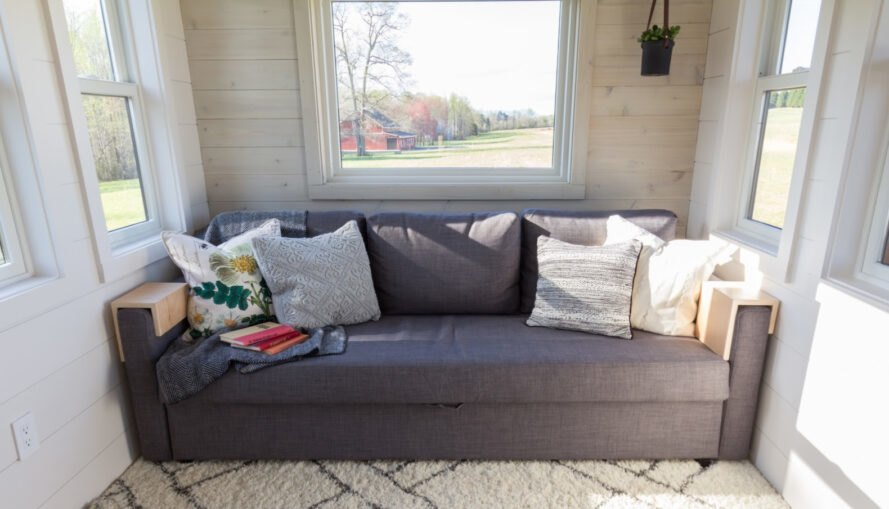 a gray love seat under a large window