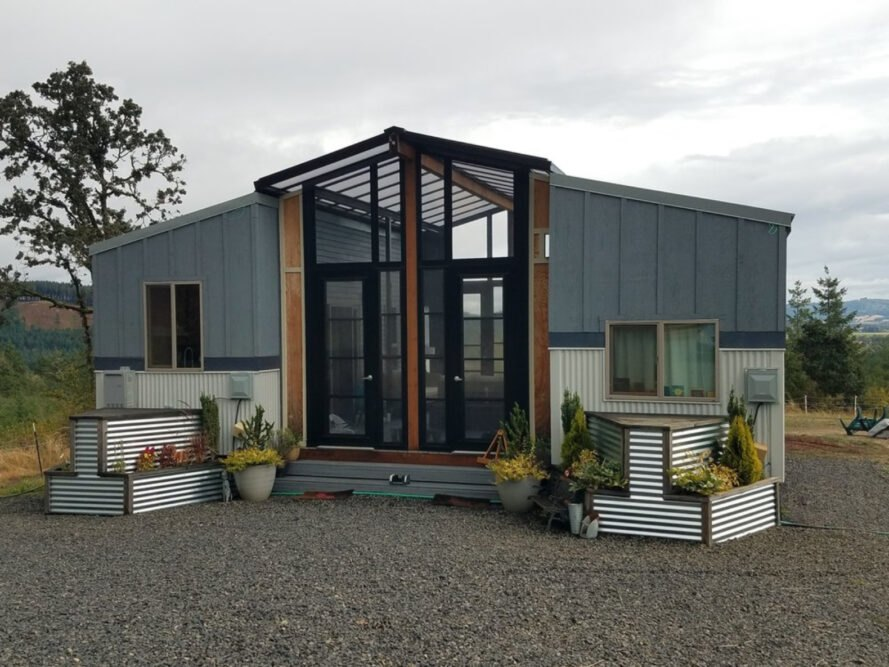 two gray tiny homes connected by glass-enclosed sunroom