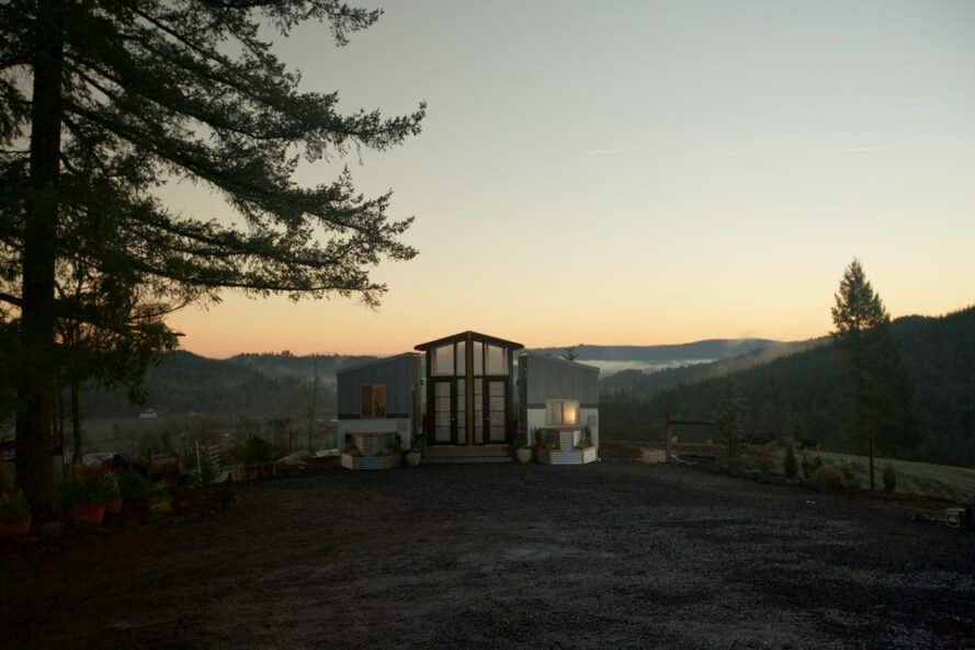 two tiny homes connected by glass-enclosed sunroom at sunset