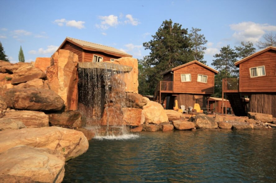wooden cabins set around a lagoon with a waterfall