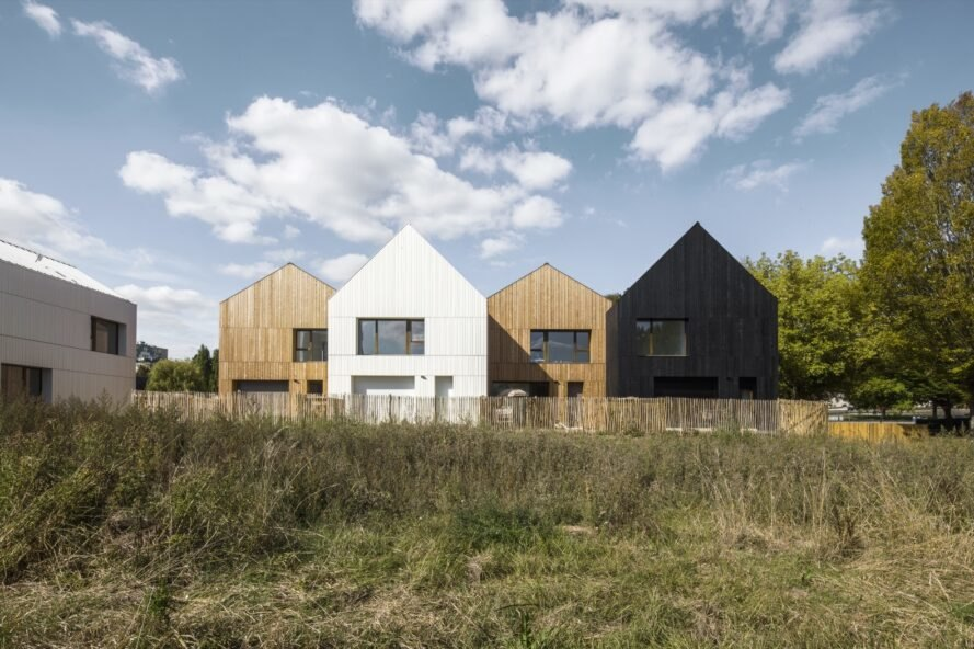 wood and straw houses surrounded by greenery with blue skies above