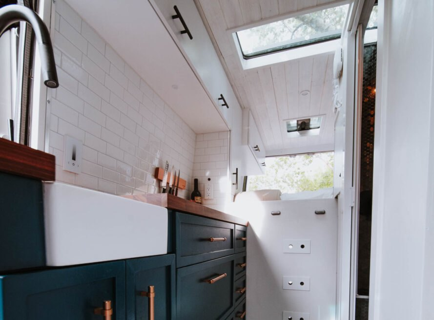 kitchen space with dark blue cabinets and white tiles