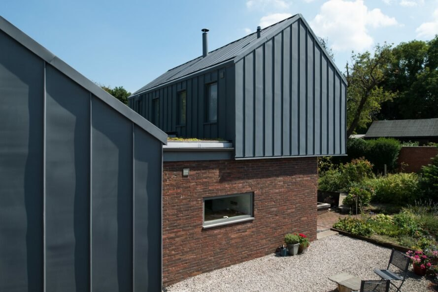 brick home with zinc gabled roof