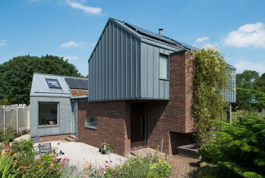 brick home with zinc roof topped with solar panels