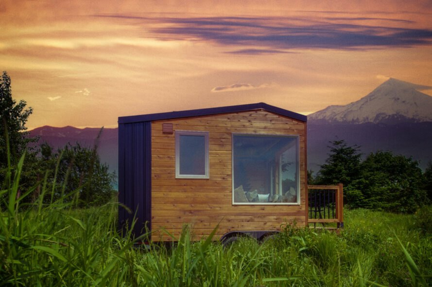 wood tiny home with mountains in distance during a pink sunset