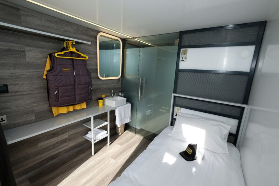 compact intierior of shipping container with a bed and small closet
