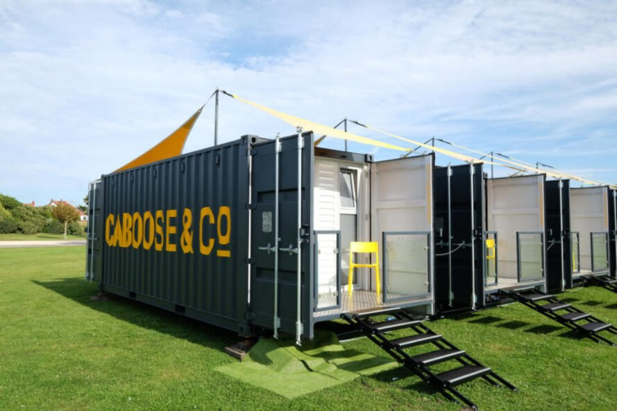 shipping container lodgings with pitched yellow roof