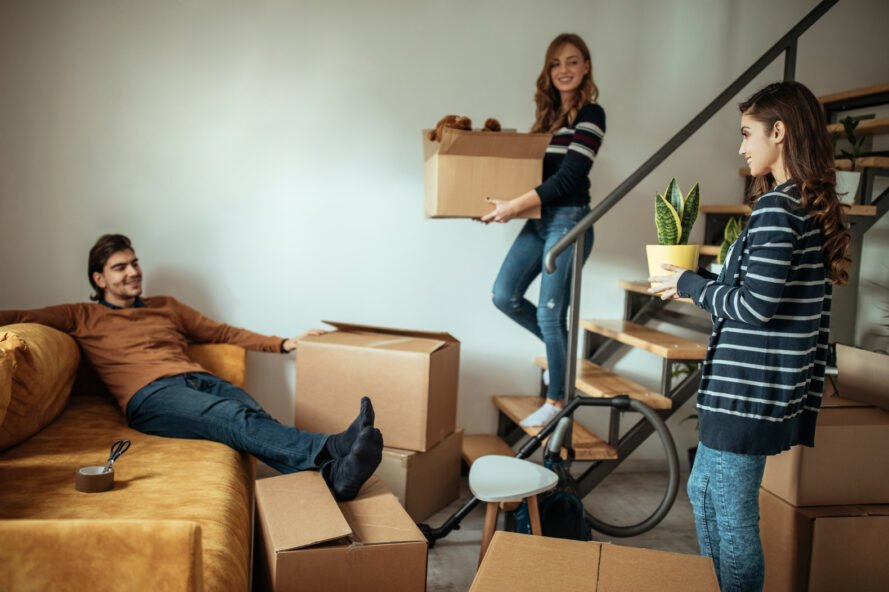 group of people moving boxes in new apartment