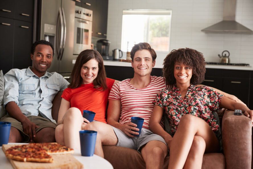 group of friends eating pizza and sitting on a couch