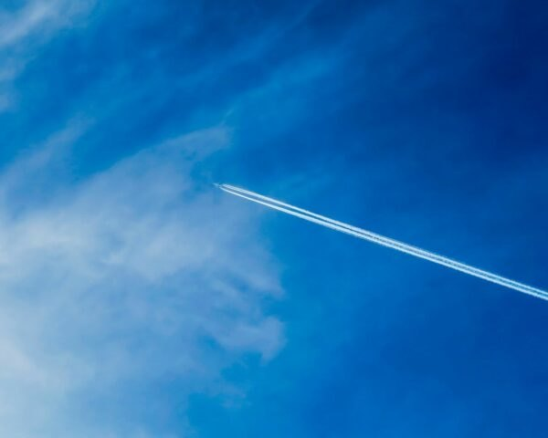 airplane emitting contrails in the sky
