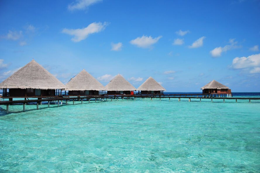 row of thatched-roof hotels over clear blue waters in the Maldives