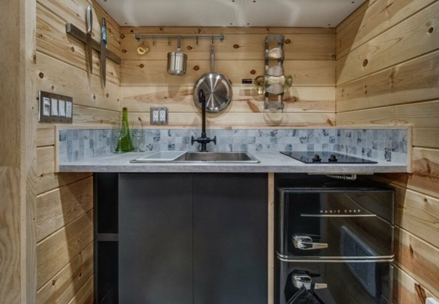 kitchen with gray-tiled counter and wooden backsplash