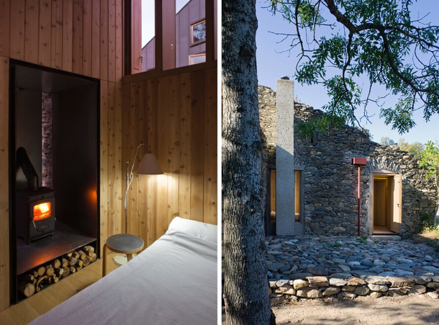 On the left, bed beside wood-burning stove. On the right, stone building near trees.