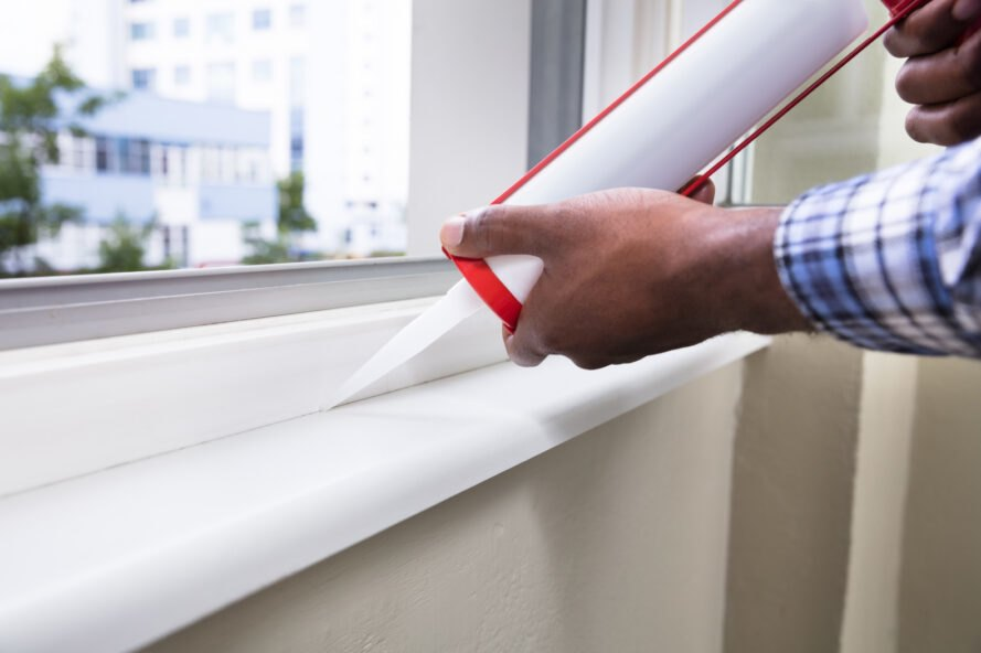 person sealing window frames