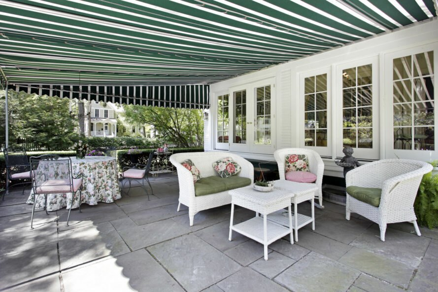 patio with lounge seats under a green and white striped awning