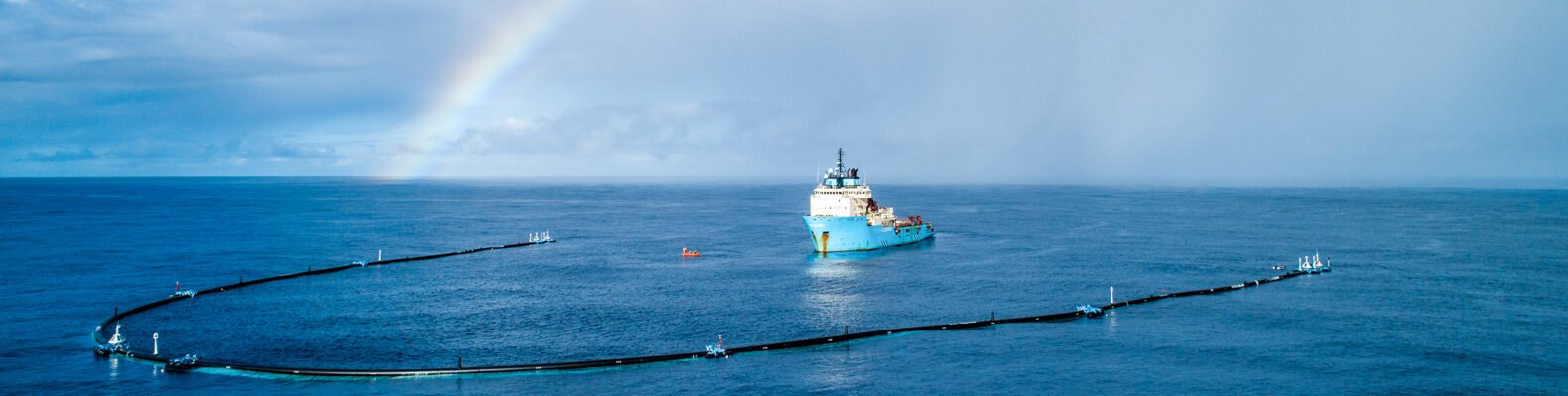Ocean Cleanup device being pulled by boat on ocean