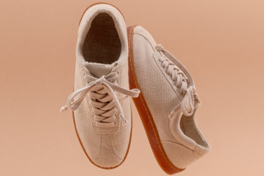 beige sneakers on pink background