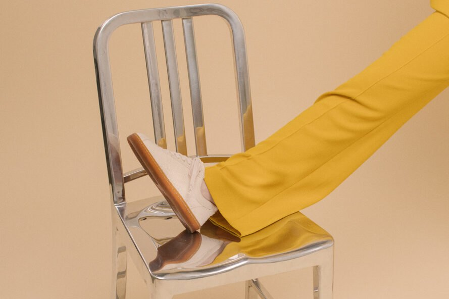 person with yellow pants wearing beige shoe with foot propped up on silver chair