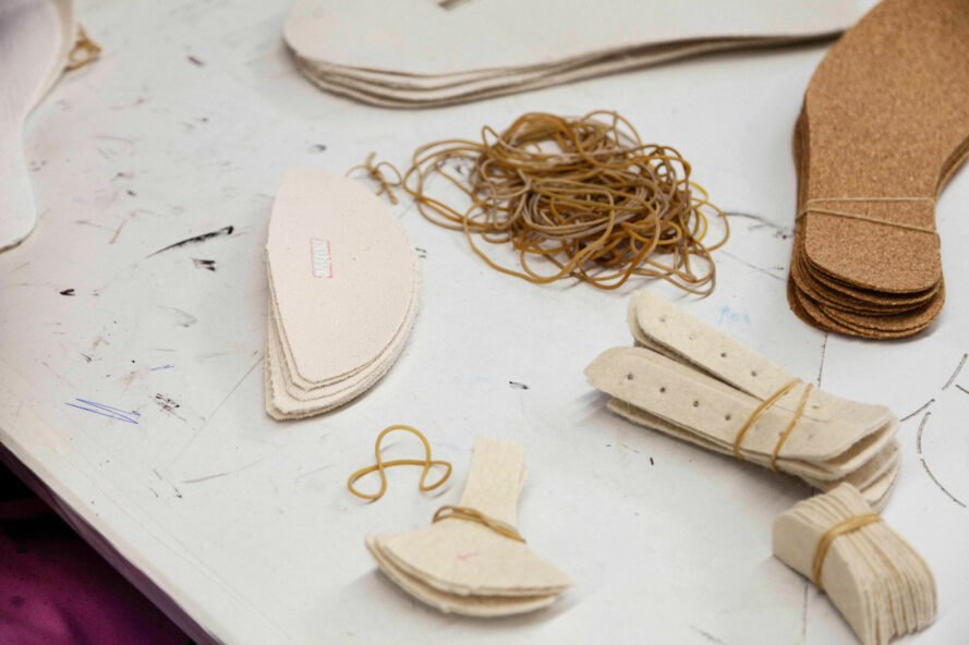 beige pieces of a shoe on a work table