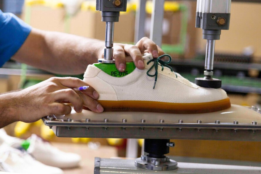 person forming a shoe in a factory