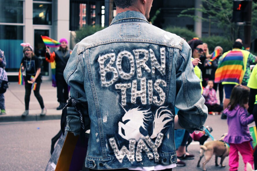 "person at Pride parade wearing DIY decorated jacket that reads ""Born This Way"""