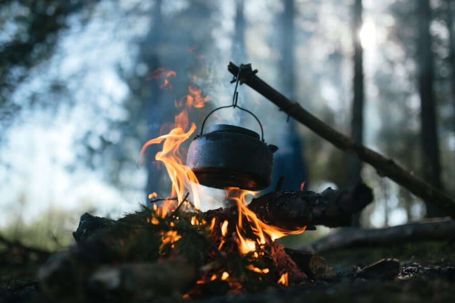 pot hanging from tree branch over fire