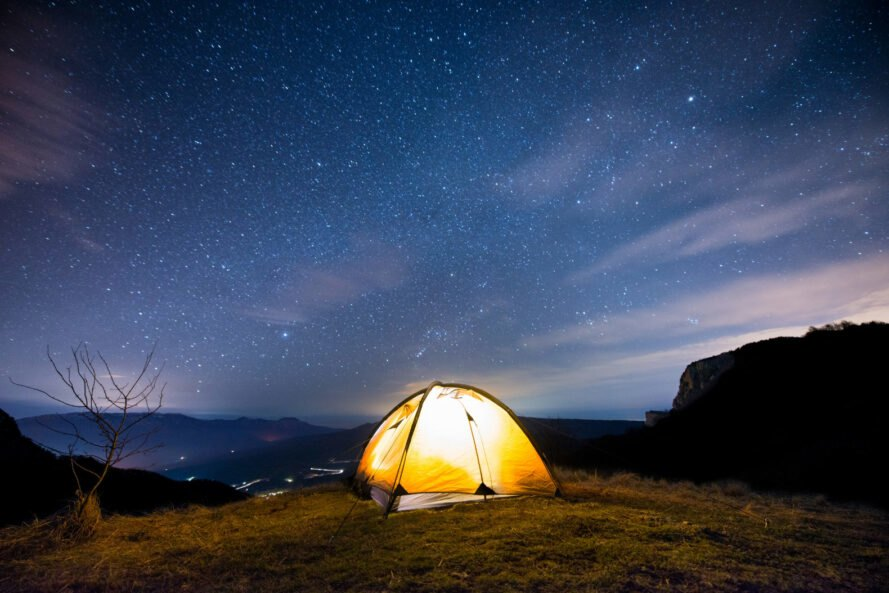illuminated camping tent near cliff with a starry night sky