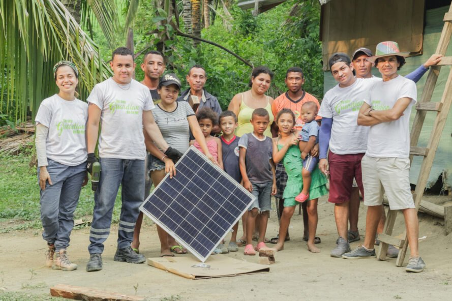 Tierra Grata members and community holding a solar panel