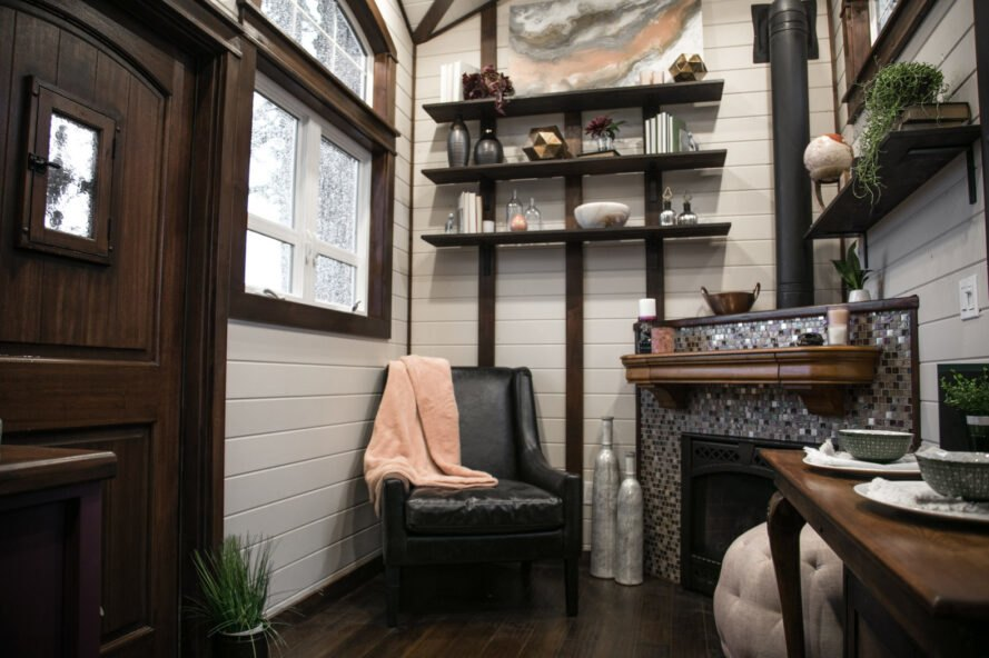 tiny house with black leather chair near fireplace and with walls of shelves