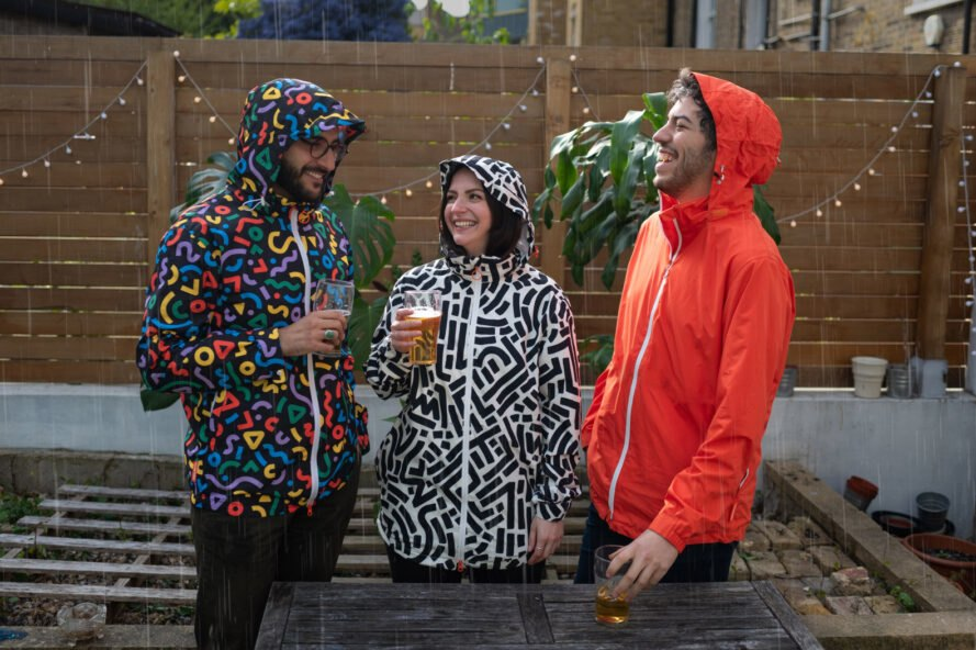 three friends in bright and patterned rain jackets drinking beer in the rain