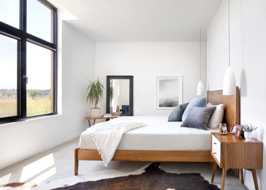 a bedroom with a bed in front of large windows