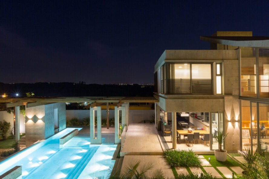 evening view of illuminated home with swimming pool