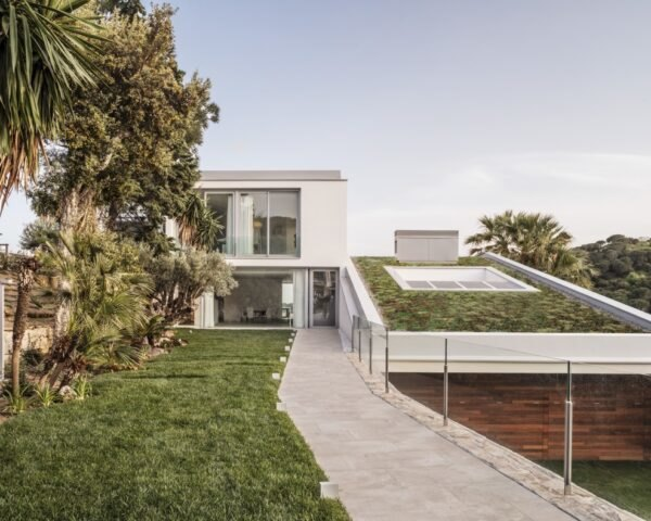 slanted white home with green roof