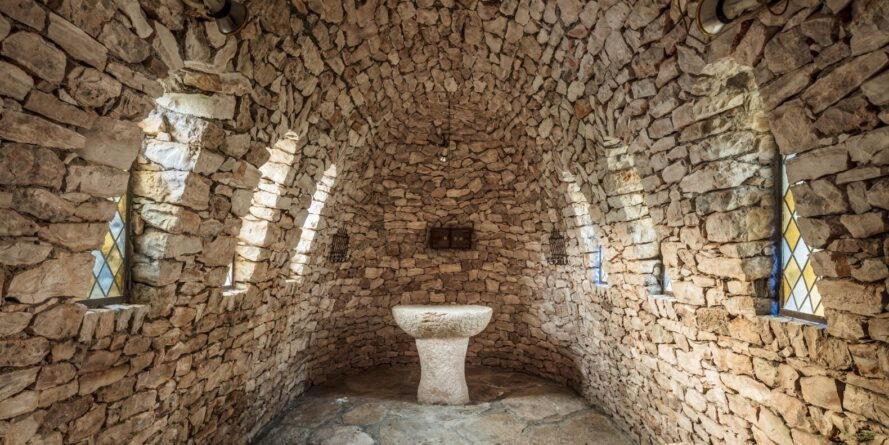 room with ancient stone walls and stained-glass windows