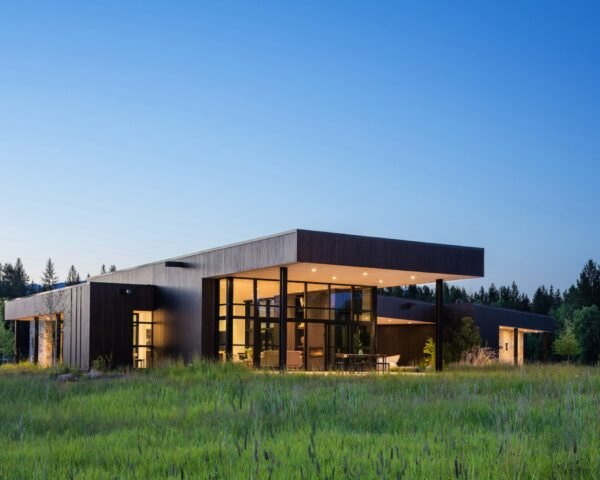 modern home with floor-to-ceiling windows is illuminated with light in the evening surrounded by grass