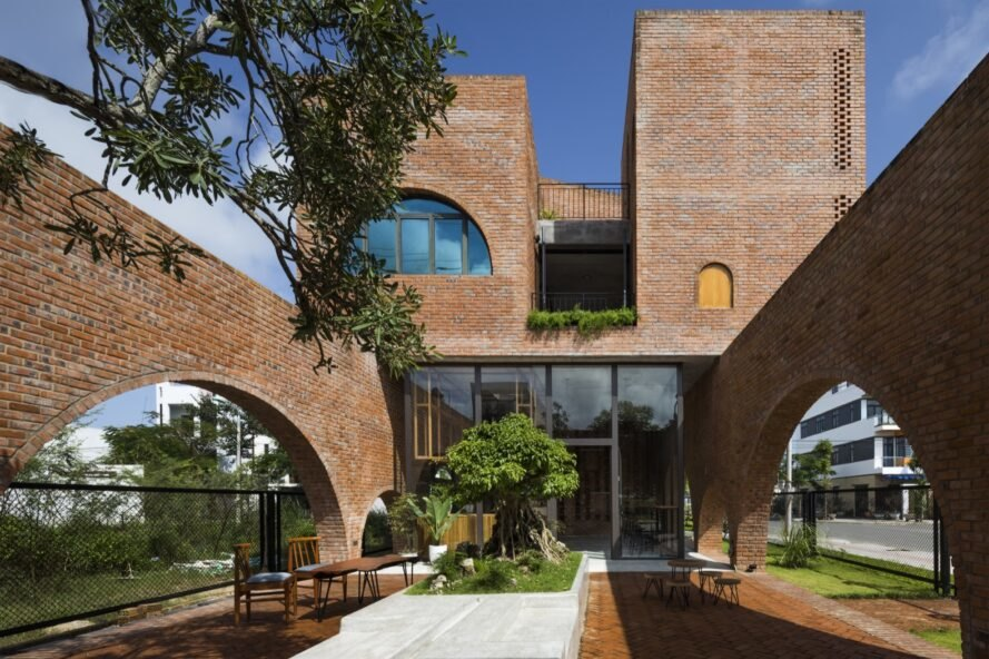linear brick home with two additional brick volumes on second story with courtyard on ground floor