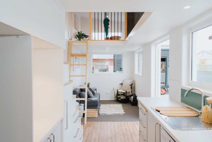 white interior of tiny home with wood ladder leading to loft