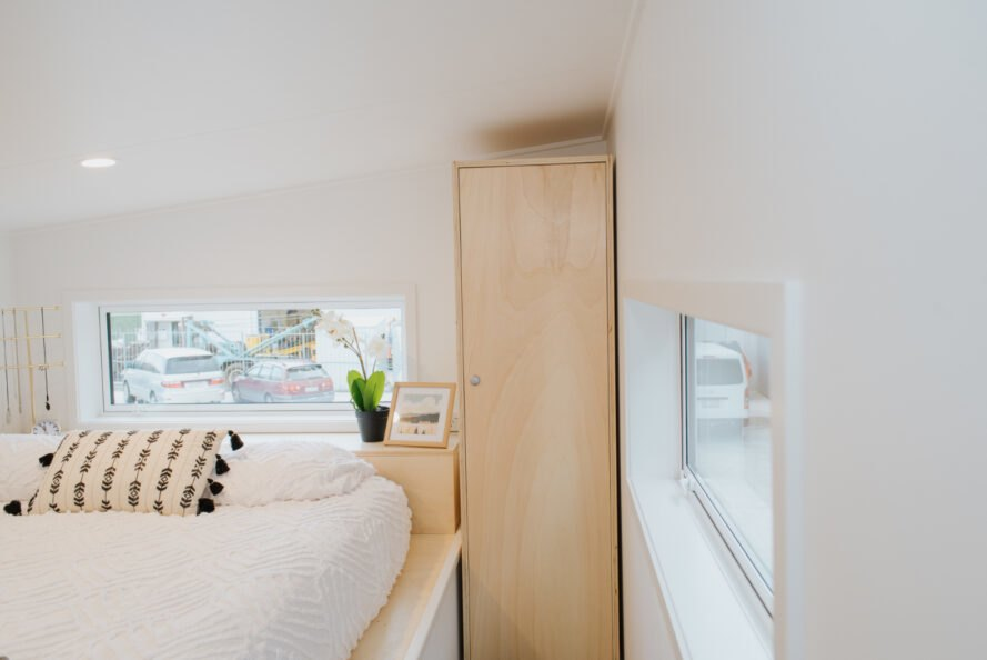 bedroom with two large windows and tall wood wardrobe