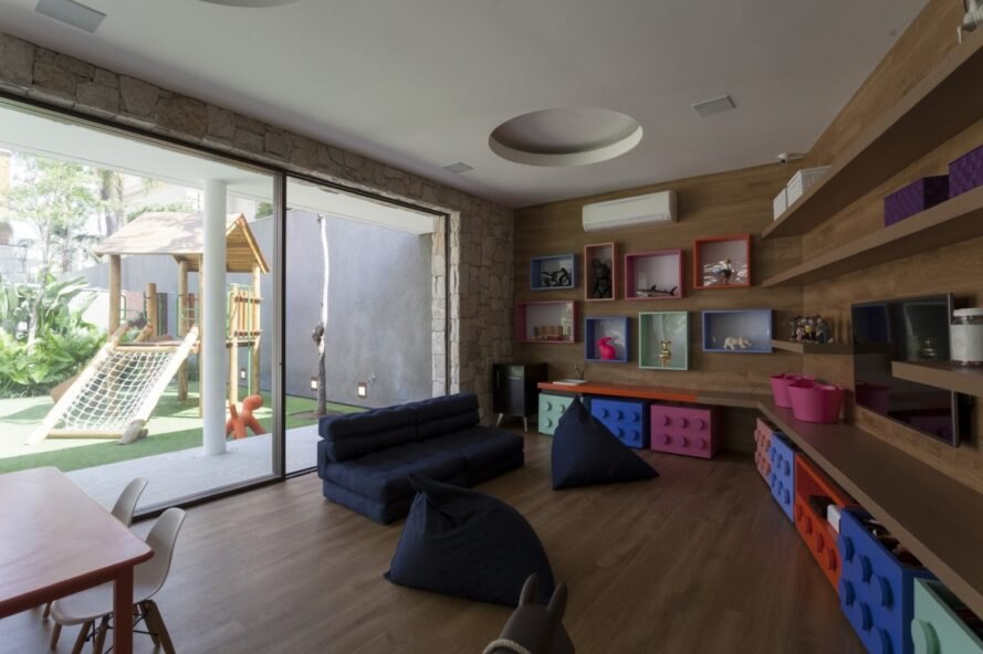 toy room with wood shelves and black sofa