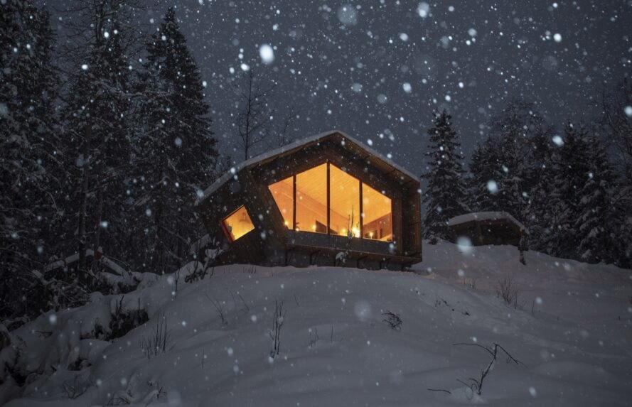 wood cabin on snowy hill at night