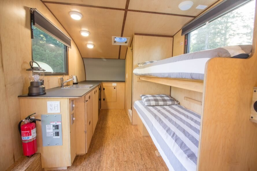 interior of wooden caravan with bunk beds and tiny kitchen