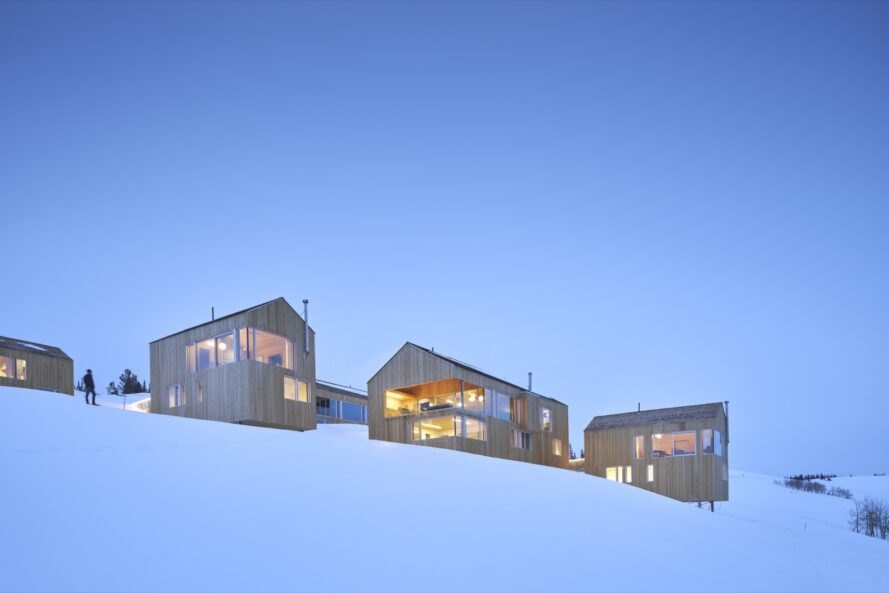 timber ski cabins surrounded by snow on a hill