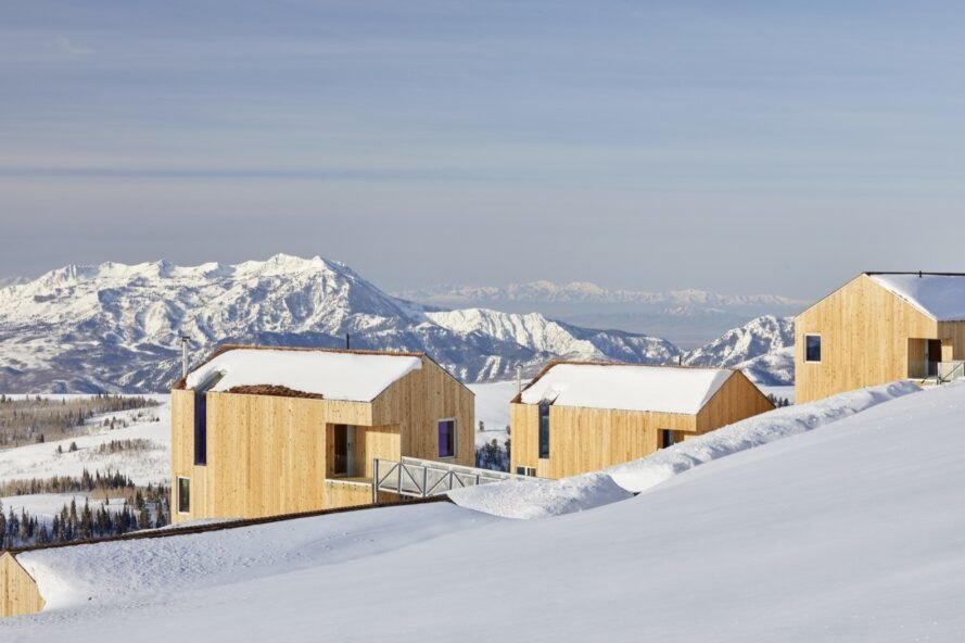 timber cabins atop of snowy mountain