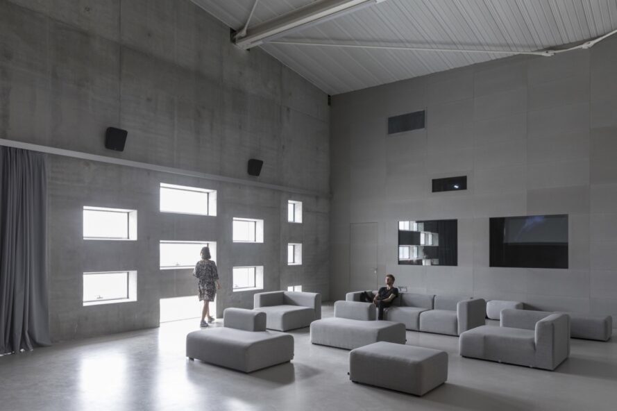 concrete room with gray sofas